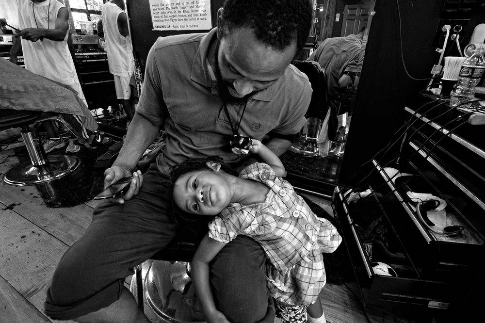 "Zun Lee,  Daniel ""ZooNine"" Poré plays with Havana Rain in his barber shop , Detroit, MI, 2012"
