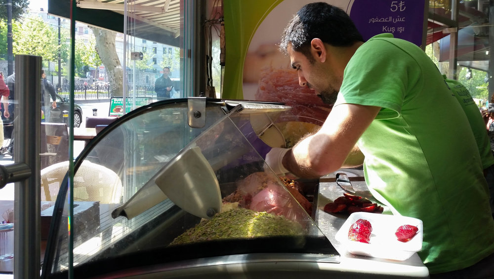 Rashed prepares ice cream by decorating freshly made mounds of it with fresh fruit and crushed pistachio. (Photo by Dalia Mortada)