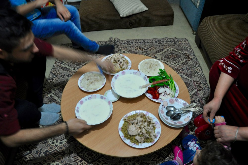 Rashed's family sets the table for a meal of ermen - or shakriyya - in their modest home in Istanbul. (Photo by Lauren Bohn)