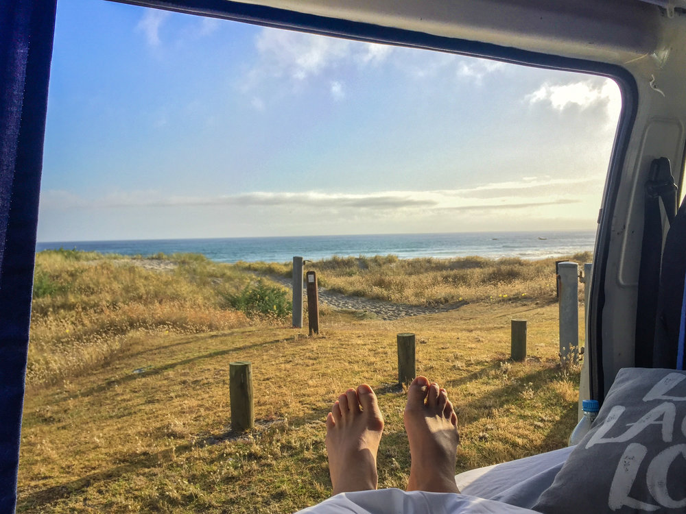 Hard backpackers life living in a van in front of the ocean