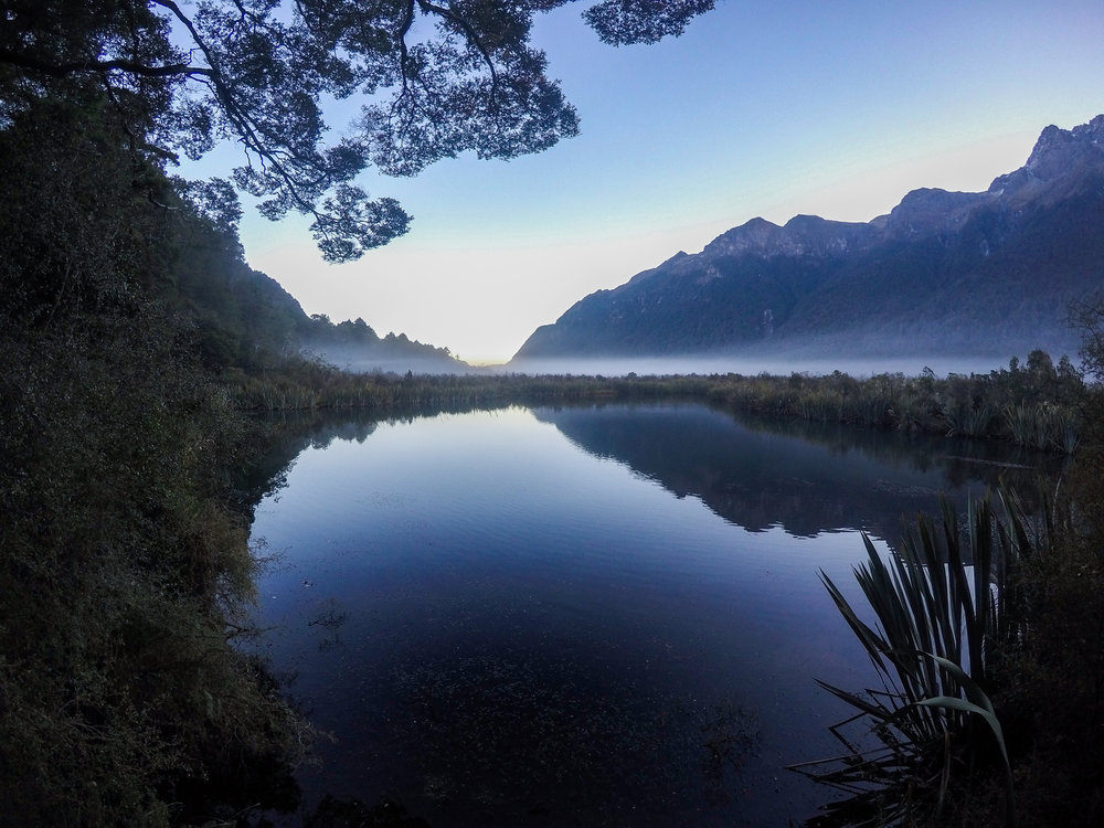 Mirror Lake reflecting mountains on the water in Fiordland
