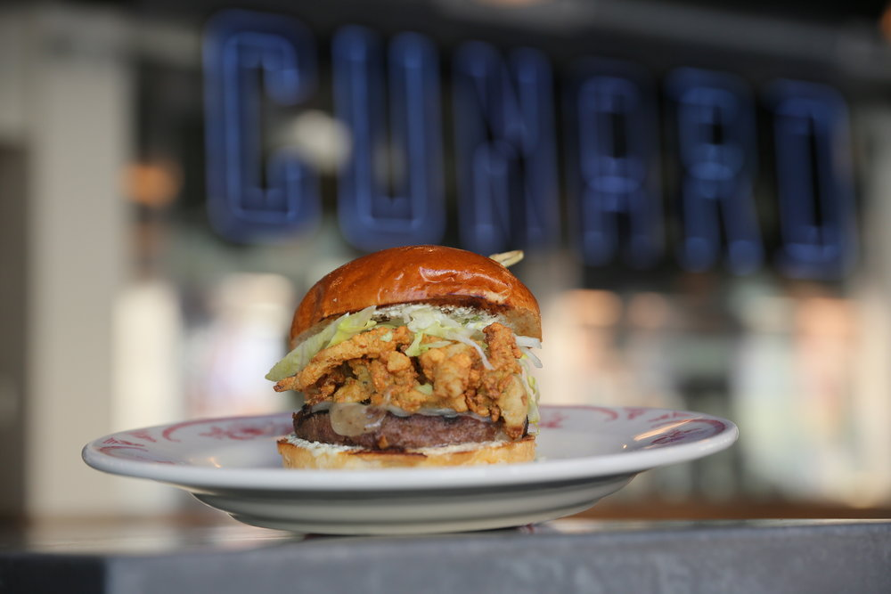 Samuel Cunard Burger: grilled beef patty, fried whole belly clams, shredded lettuce, swiss cheese, house made tartar sauce on a toasted brioche bun.