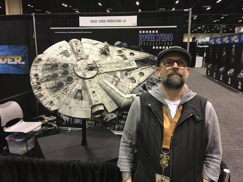 Jason standing next to the Millennium Falcon model built to scale by Rogue Studio Productions