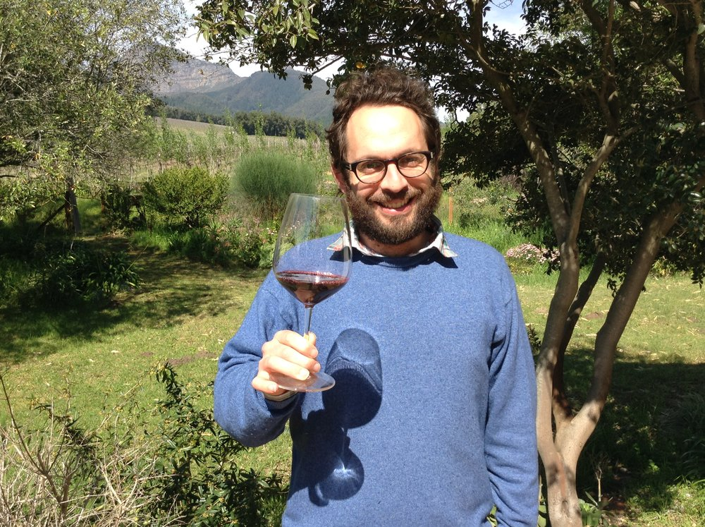 Simon Back, who is among the fourth generation to helm Backsberg Wines & Estates, stands on his deck in Paarl, South Africa, raising a glass of Merlot with his merlot vineyards behind him.  Read more:  http://forward.com/food/321145/making-wine-at-the-end-of-the-world/