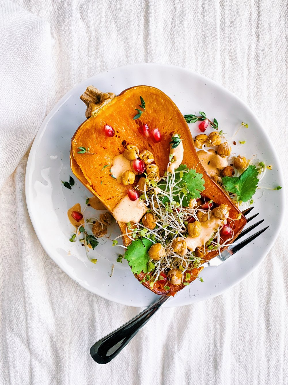 Honeynut squash with crispy chickpeas, citrus tahini dressing, pomegranate, herbs, and sprouts! A delicious plant based dinner!