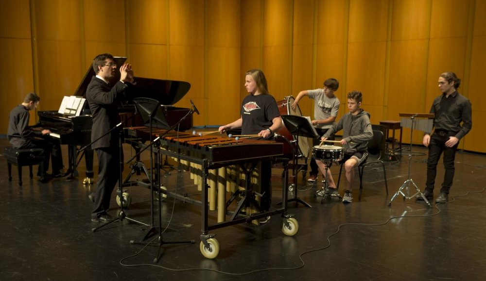 """Jon Nelson, second from left, talks to composer and pianist, Ryan Sellek, Bella Wineke, Jonathan Foster, Griffin Langhan, all 9th graders, and Jacob Couch, 11th grade, during a rehearsal of Resonance 2018 at the Sun Prairie Performing Arts Center. Sellek's composition is titled, ""The Sunken Meadows March.""  ANDY MANIS, FOR THE STATE JOURNAL""   (Source: Wisconsin State Journal)"