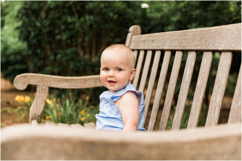cute baby smiling on a bench