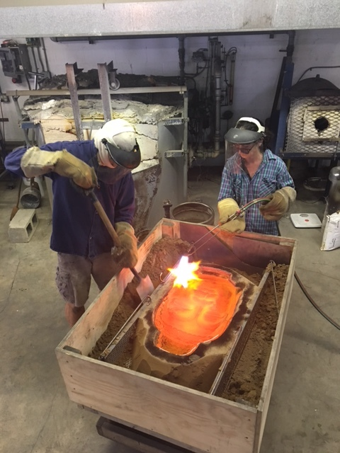 Marlene torches the glass while her husband, Thomas, cuts away the excess portion of the sand mold