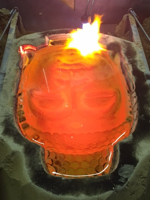Close-up view of the Buddha head being torched.