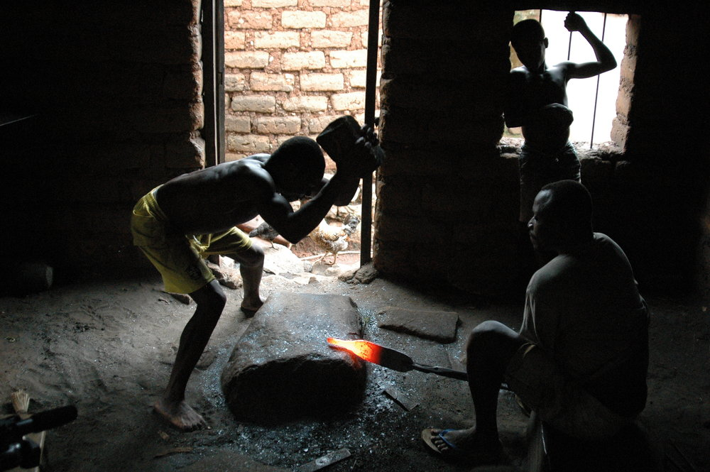 Kossi Kao and assistant, Essozimna Ide, rough out initial forging of an initiation bell. Tchare, Togo. © Tom Joyce, 2010.