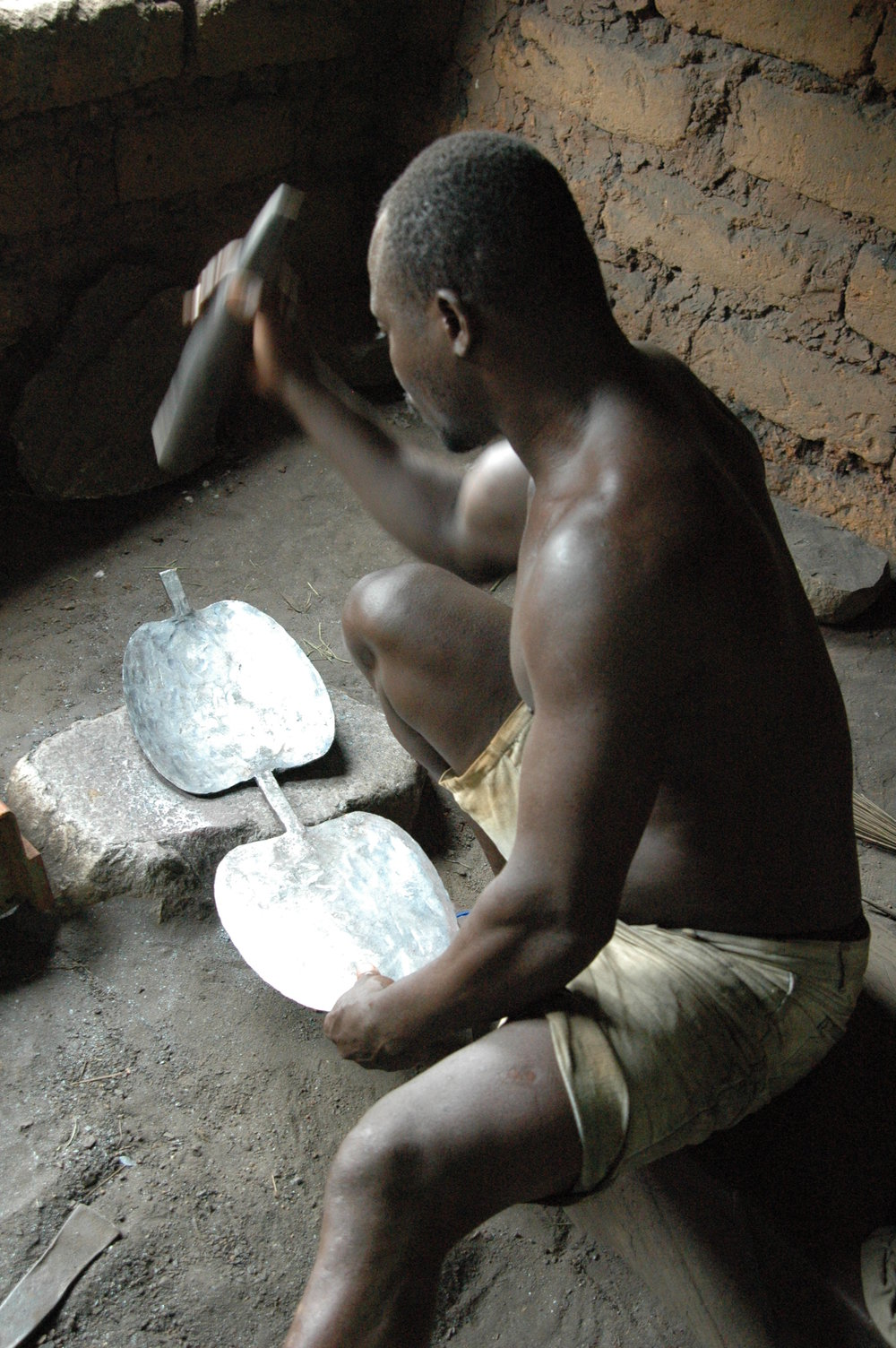 Kossi Kao cold planishes the initiation bell before folding the two halves together. Tchare, Togo. © Tom Joyce, 2010.
