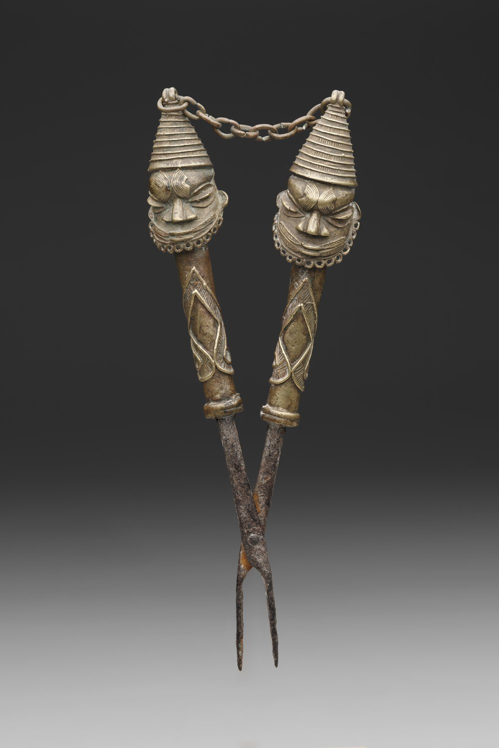 Artist unknown (Yorùbá peoples, Nigeria), figurated tongs for Òṣùgbó Society, early to mid-20th century, iron, copper alloy (cast). Dallas Museum of Art, 2005.92, Gift of George and Sidney Perutz in honor of Roslyn A. Walker