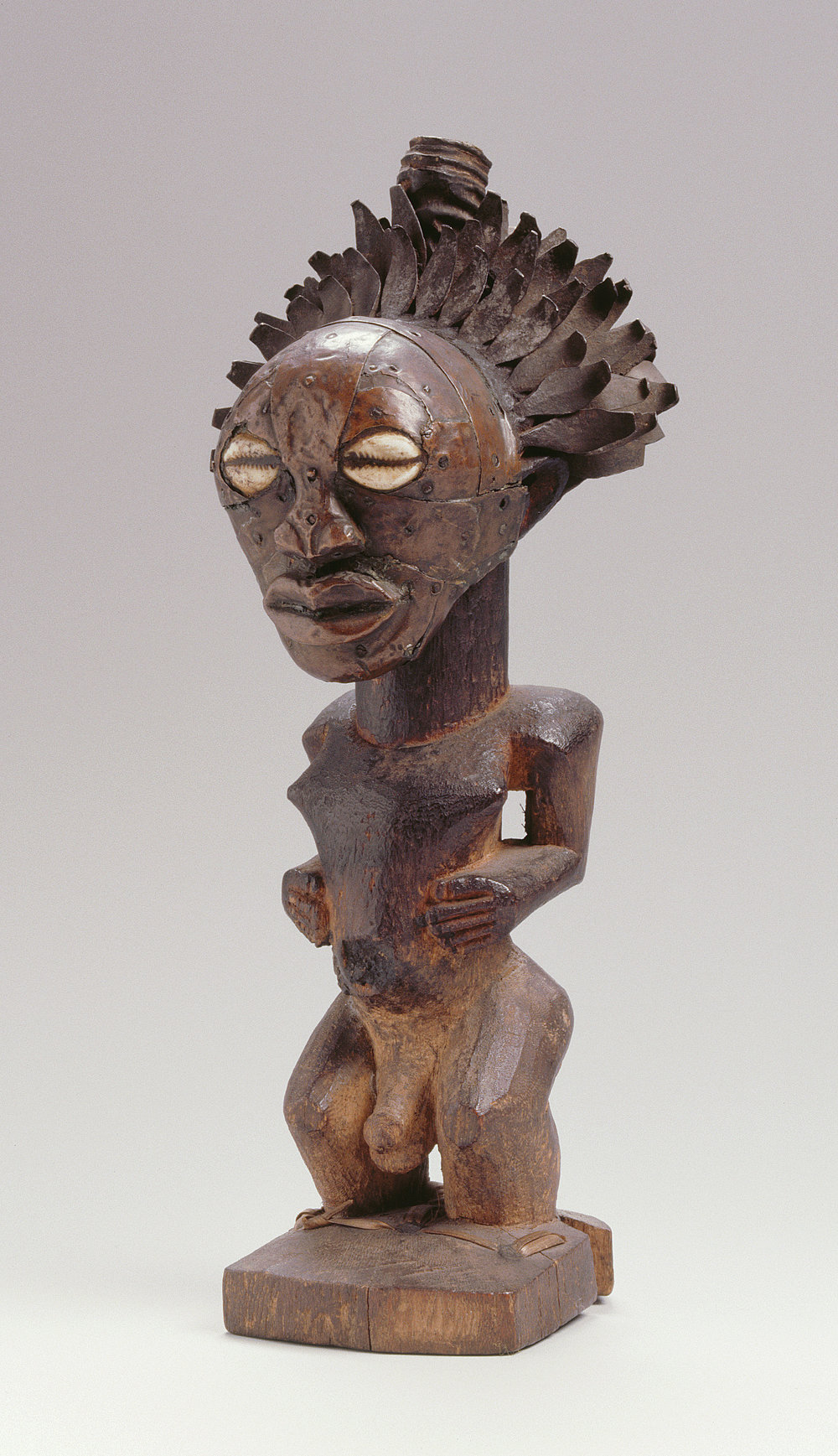 "Artist Unknown (Songye peoples, Democratic Republic of the Congo), Nkishi figure, mid to late 19th century, wood, forged iron, copper alloy, cowrie shell, horn, H: 28.5 cm, W: 12 cm. Collection of the MAS, Antwerp, Belgium (AE.0720), Gift of Louis Franck, Antwerp, 1920. Image © MAS | Museum aan de Stroom, Antwerpen. Photograph Michel Wuyts, 2016. Provenance: Field collected in 1920 by Louis Franck (1868-1937). Selected for the Belgian Pavilion at the New York World's Fair of 1939, nicknamed ""the man with iron hair."""