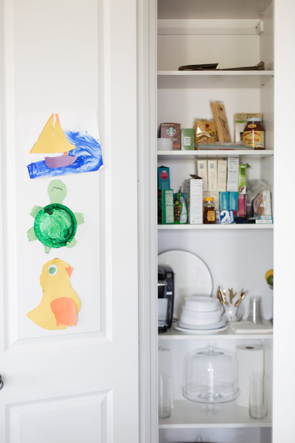 Her son Beck's artwork is a happy welcome into the pantry, which also stores her Keurig, microwave, and toaster.