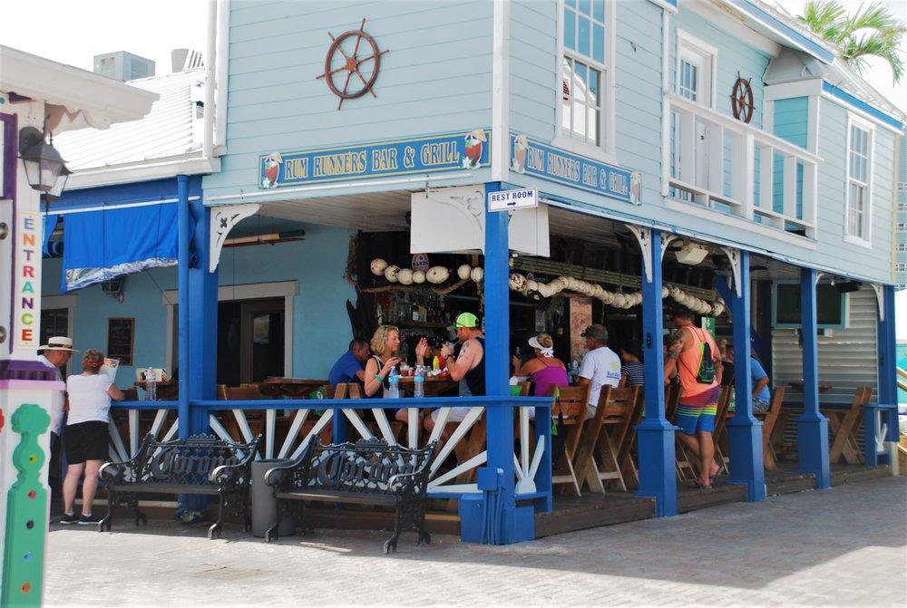 Tourists enjoying outdoor dining at Port Lucaya
