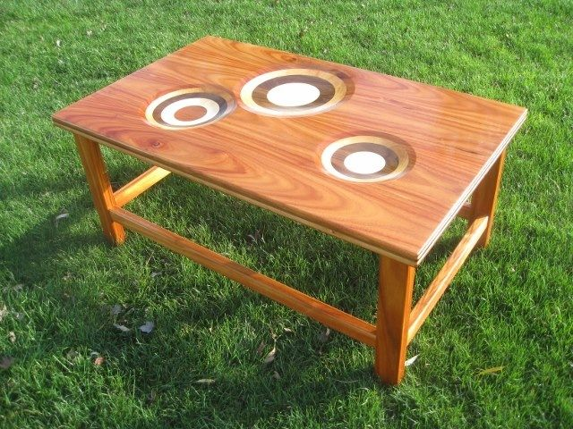 "Coffee table made from five different woods: Monkey wood, Cherry, Walnut, Maple and African Mahogany. The scoops and the edge depict the 5 layers. 45"" x 27"" x 20"""