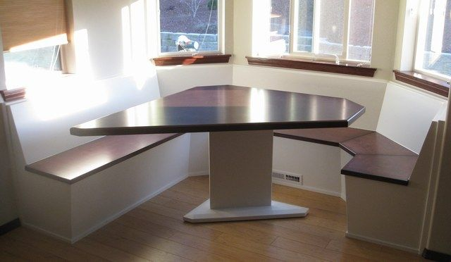 """Custom table and bench tops from Alder wood and stained it while the rest of the project was painted white. The bench tops open on piano hinges for easy access for storage below. 8' x 8' seating and 30"""" h table"""