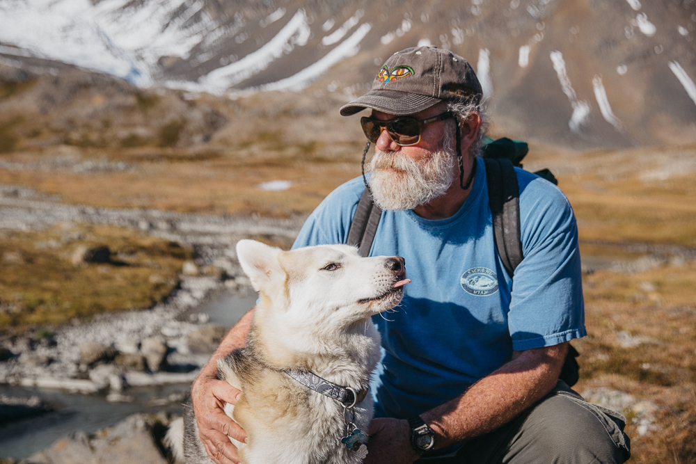 """I met Steve and his dog, Tundra, about 5 miles up in the mountains. It was his day off so he took the long hike... mostly for his dog. (Steve constantly needs to come up with ways to tire off the energetic husky.) We shared some water as we took in the sights. I found out that Steve moved to Alaska from Arizona almost twenty years ago. He fell in love with the land and its people, something I can definitely relate to. His respect for Alaskans came through when, at one point in our conversation, he told me that """"Alaskans are resilient and very deliberate people"""". Those must be essential qualities on a land where conditions are harsh and the concept of time is diluted between the winter and summer months... but I'm sure there is much more to it."""
