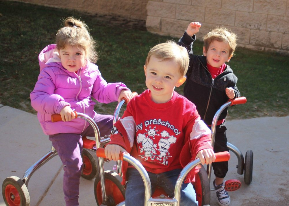 Riding tricycles on the preschool playground