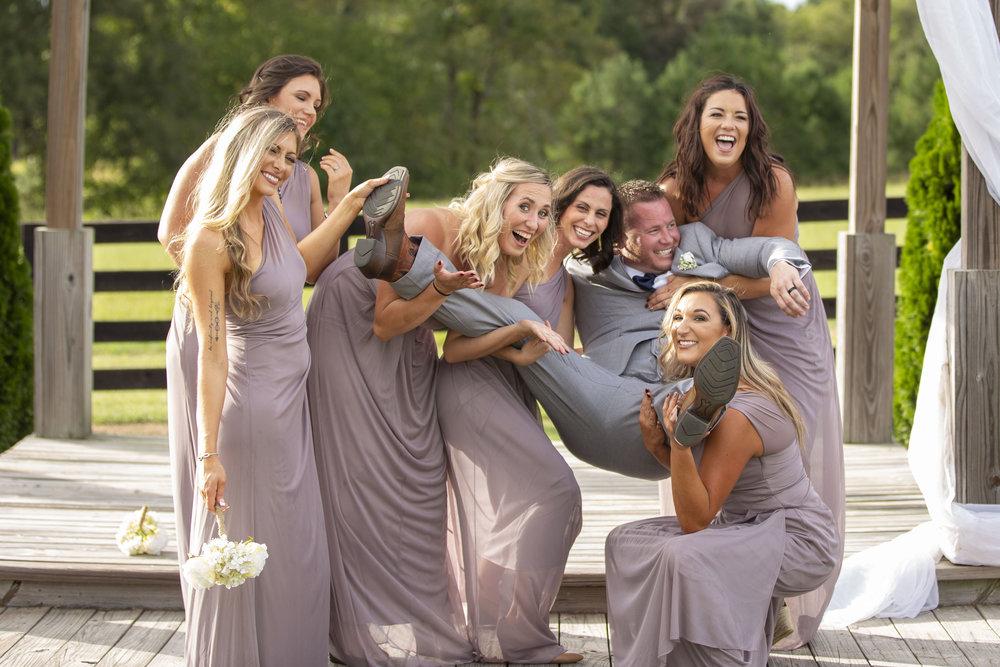 bridesmaid-holding-groom-laughing.jpg