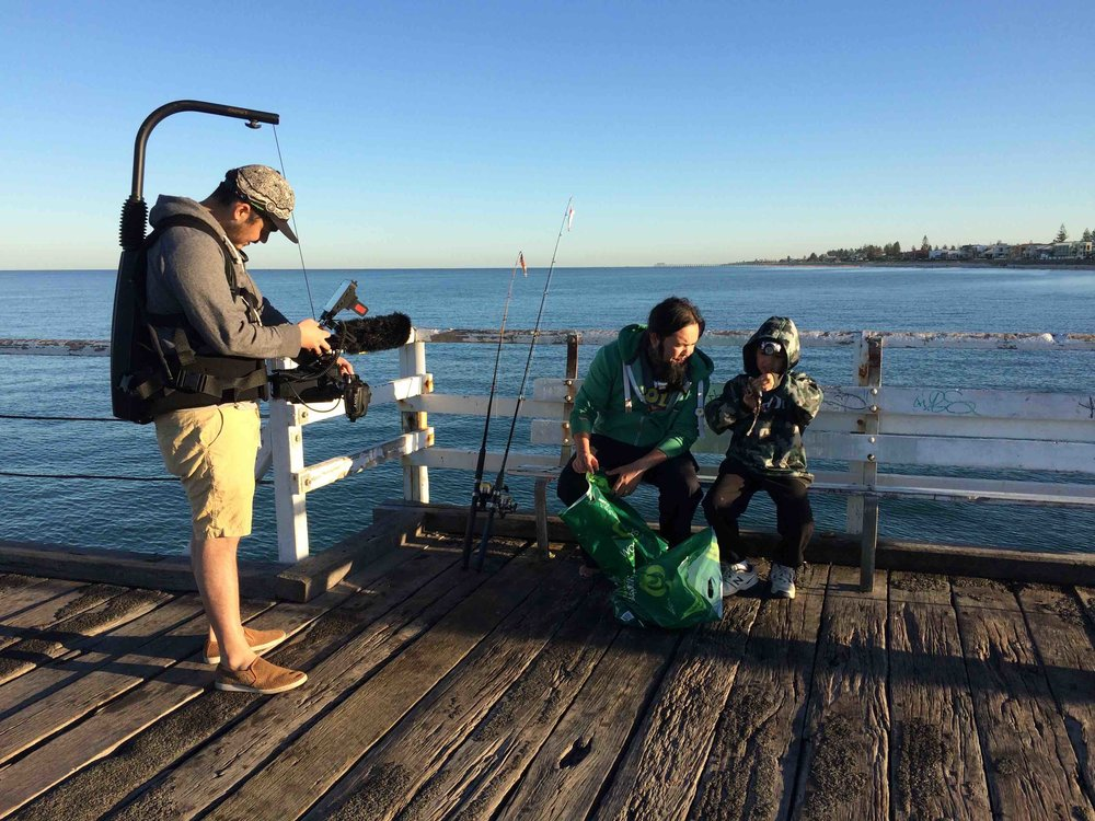 Damien and his son with our DOP and director Johanis at Glenelg Jetty. Photo Carl Kuddell