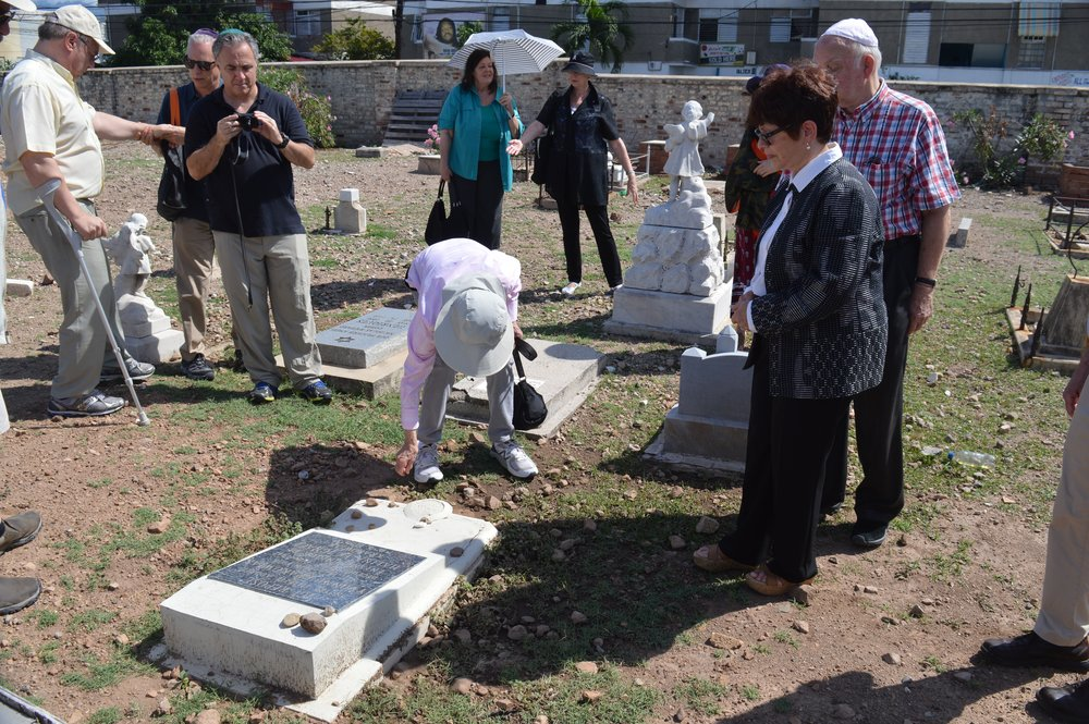 "During the ""Reunion"" of Gibraltar Camp 2 internees and descendants of internees, organized by Prof. Diana Cooper-Clark in November 2016. The group visited the Orange Street Cemetery. This was the first time that a proper  Kaddish  was said over my sister Yvonne's (ZT""L) grave by a  minyan.   Ainsley Henriques (in the checked shirt) and his step-brother David Matalon (not pictured here) are the wonderful persons responsible for arranging for a new stone to be placed on her grave. The original stone had been stolen years before."
