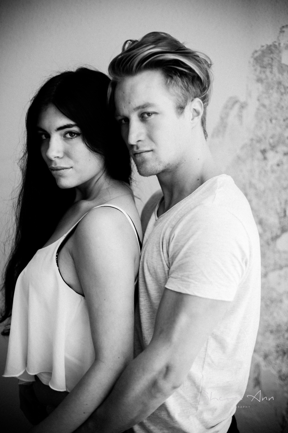Black and white portrait of beautiful hipster couple in soft window light