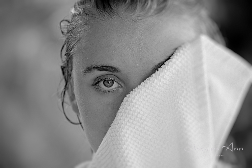 Summer time down by the pool, black and white portrait of beautiful girl drying her eye.