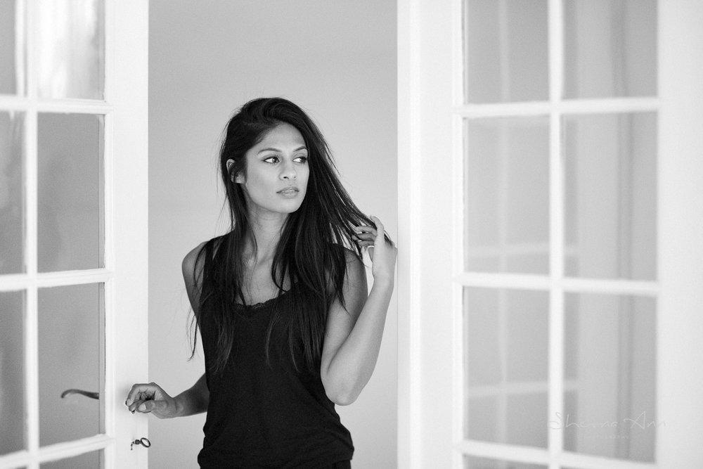 Gorgeous woman opening glass door in black top