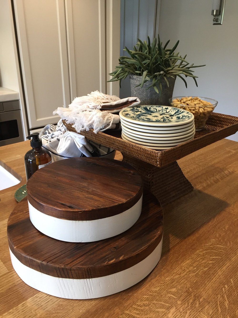 Perfect example of what to do on an island. Love these round cutting boards with the woven pedestal