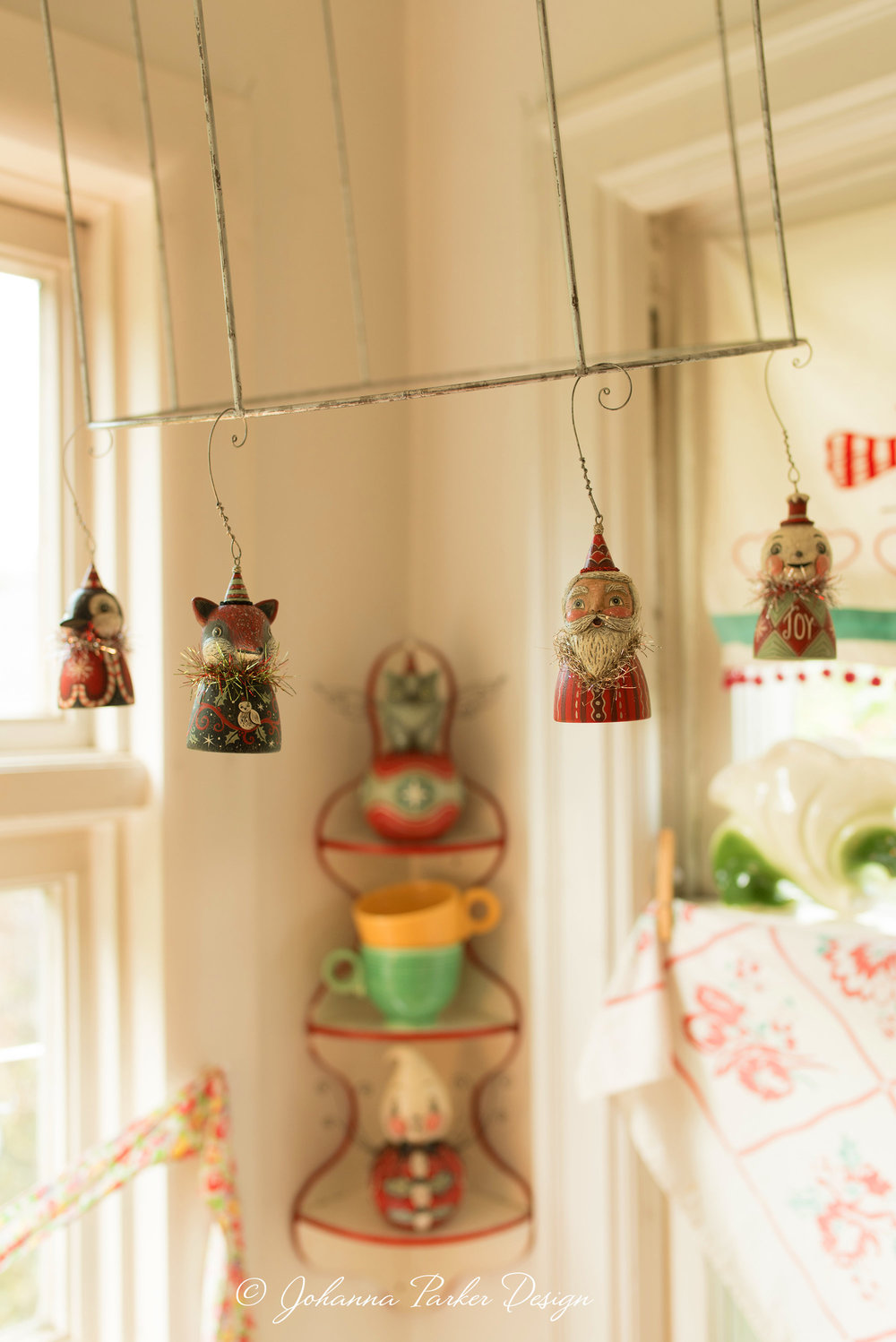 In the corner, the bare bones of an old lampshade offer easy hanging for a handful of my original ornament bell characters.
