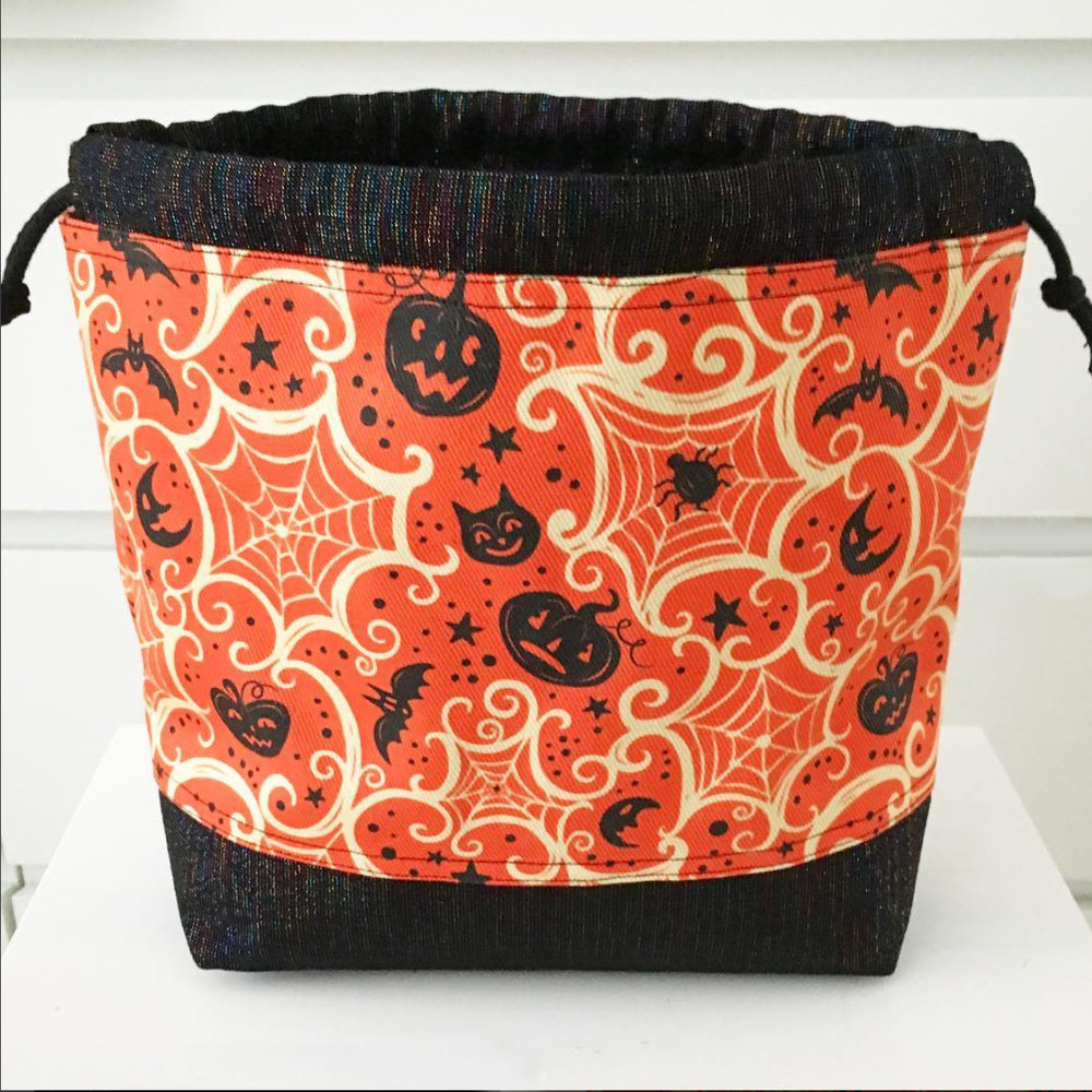 "Handmade project bag by @pinokin (on Instagram) using Johanna Parker Halloween fabric from Spoonflower.  GET: ""Spooky Cobwebs Cream on Orange"""