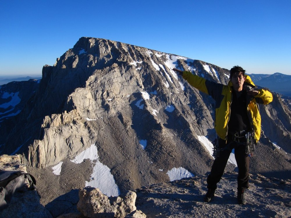 Scotty at home in his yellow jacket, on top of Mt. Russell, with a rooftop view of Mt. Whitney