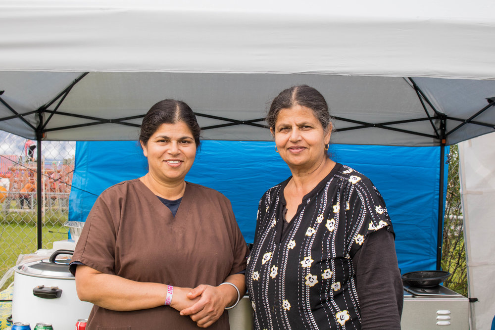 Vicky Dhillon and her friend Sweety Sidhu standing outfront their food stand.