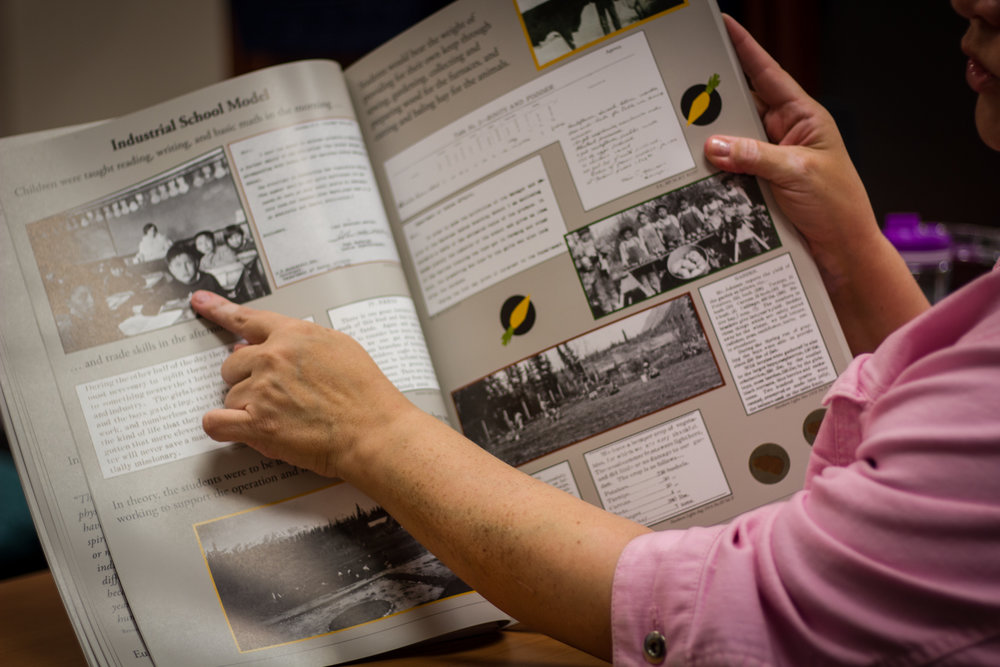Isaac looks at a book on Residential Schools, using visual aids to show what life was like for these children.