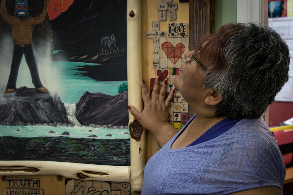 Healing is done through many ways. Here, Henry gazes up at a piece of art made by several members of different Indigenous communities.They find healing in creative collaboration, giving them a sense of community