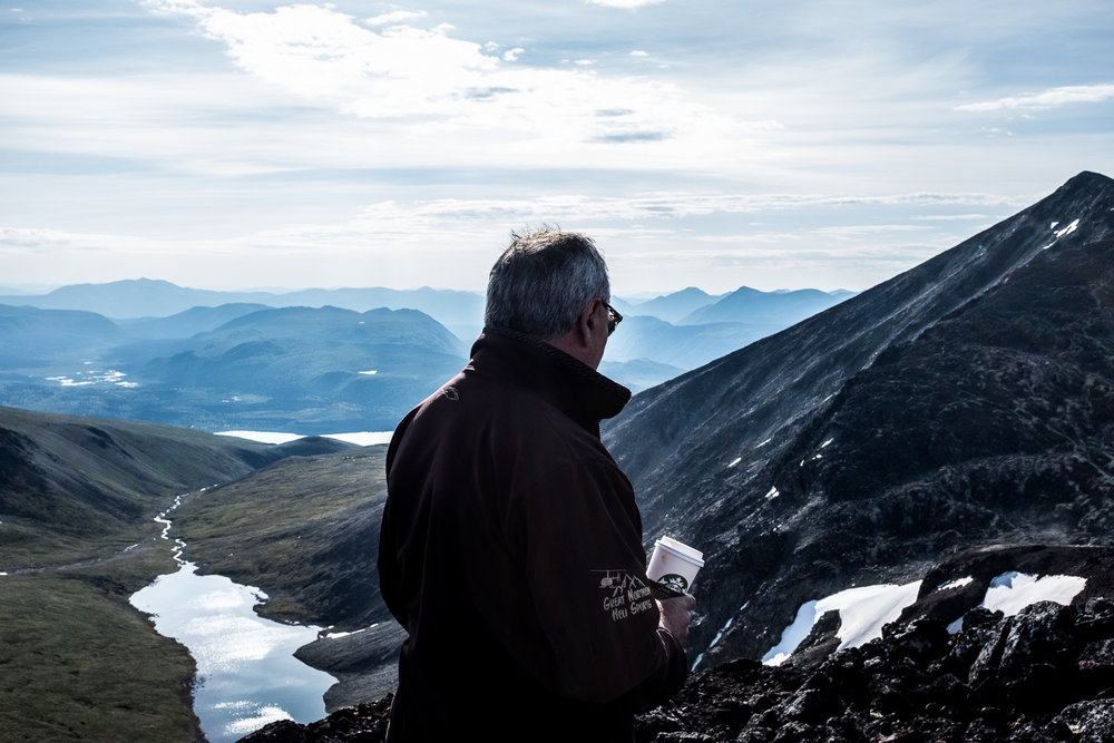 Washington enjoys the view and a cup of coffee while stopped on a glacier patch.