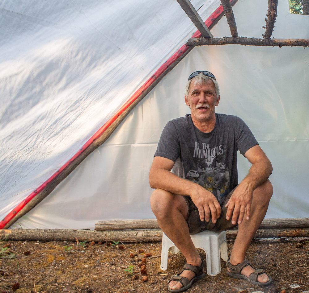 Jeff Glaeser sits in the tent where he dries and smokes the salmon they catch at the fish camp. The former British Columbian moved to the Yukon to live with his partner Dorothy Sam. Photo by Kiera Kowalski