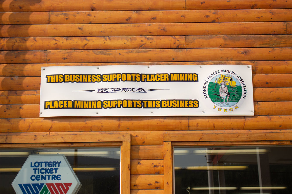 Many businesses in Dawson City hang banners showing their support of placer mining. Photo by Caroline Mercer