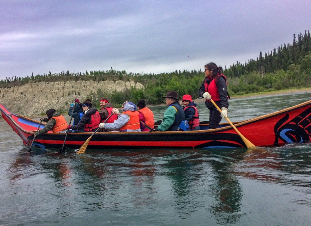 Indigenous and non-Indigenous youth and elders paddle down the Yukon River during the River Nation trip. The First Nations communities worked together to build water vessels to carry themselves and their supplies for generations. During these trips, elders would tell stories about their ancestors and share teachings on how to survive and respect the land.