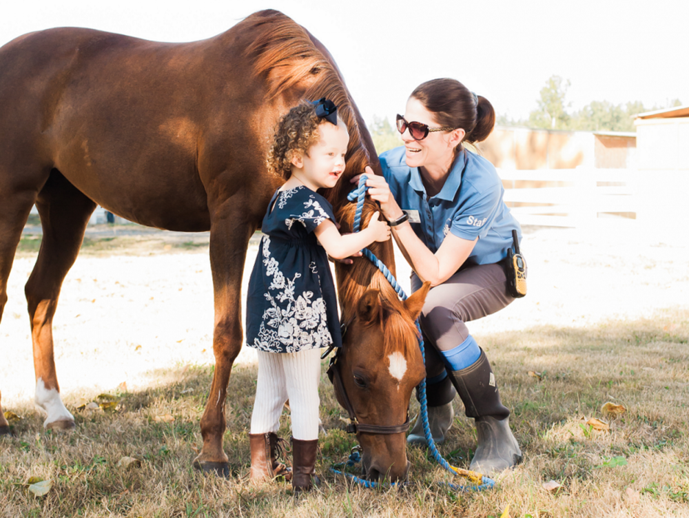 A little girl interacting with a brown horse and a Little Bit staff member.