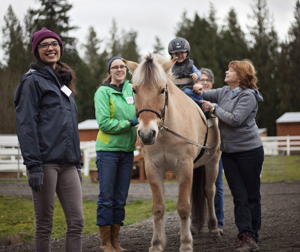 Toddler riding a tan horse outside, with his therapist, horse handler, and two volunteer sidewalkers supporting him.