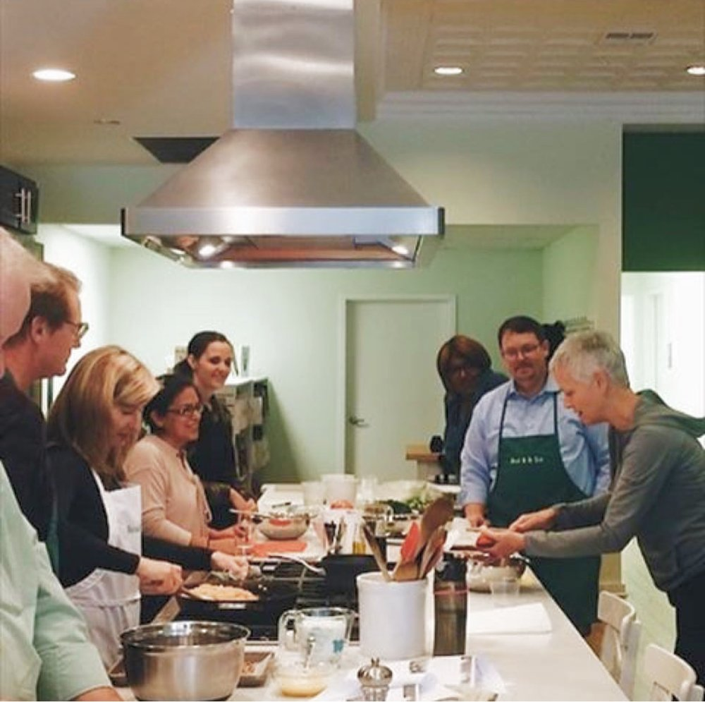 Robyn, in the gray hoodie, teaching a cooking class at Chicago's Read It & Eat It culinary book and experience shop.