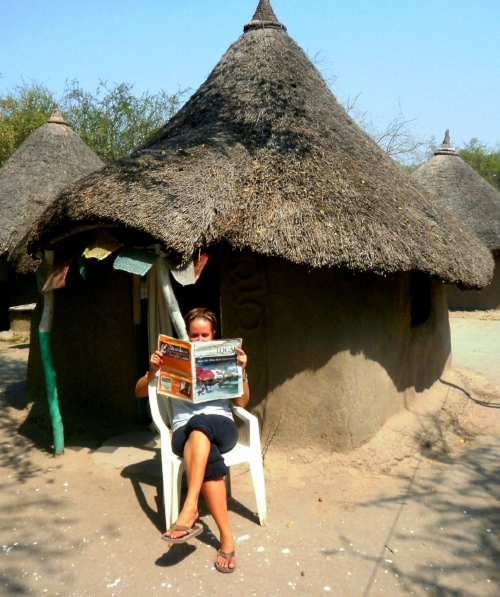 Reading The Local (Steamboat Springs) paper in front of my  tukul  (mud hut) in Jonglei State, South Sudan, early 2011.