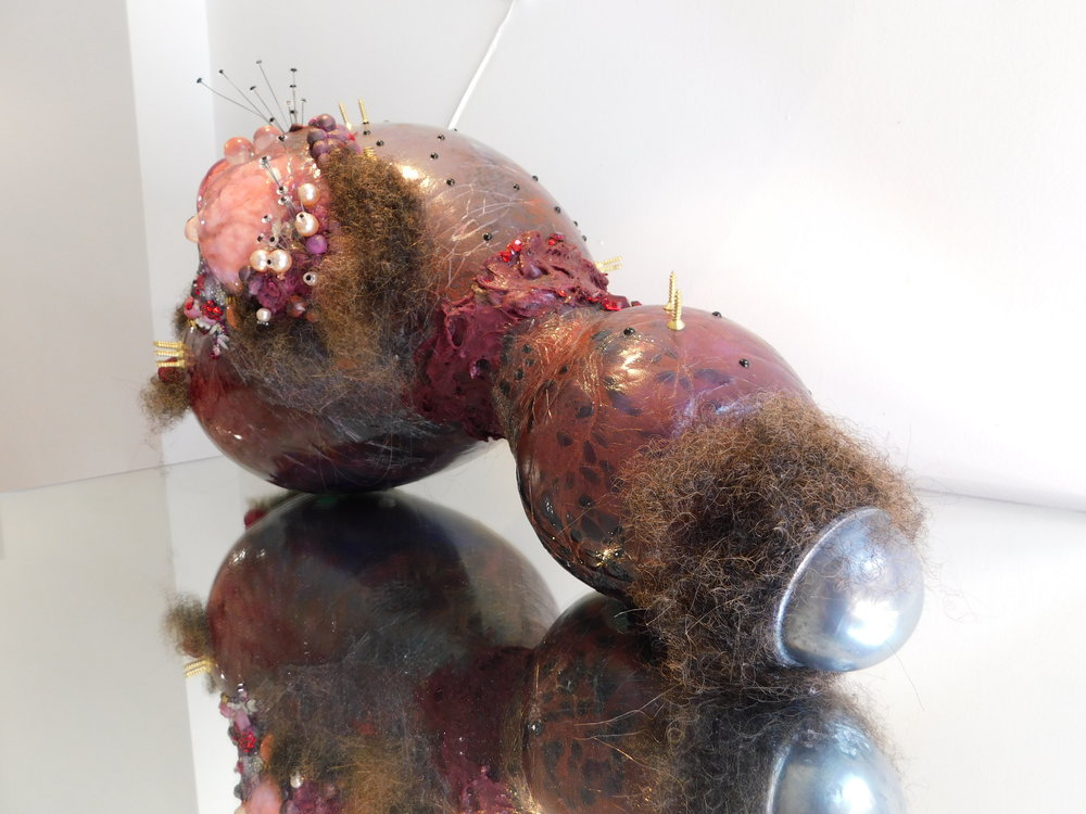 Doreen Garner,  Big Pussy (From the Back)  (2015), glass, polyester fiber, Swarovski crystals, Swarovski pearls, hair weave, teddy bear eyes, silicone, electrical parts, condoms, latex tubing, acrylic dentures, rubber gloves, glitter, brass screws, 24 x 16 x 16 inches. Photo by the author.