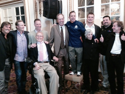 Dave McGillivray with Boston sports legends during a John Hancock function at the Fairmont Copley Plaza Hotel on Sunday night. From left to right, Dennis Eckersley (Red Sox), Steve Lyons (Red Sox), Bob Sweeney (Bruins), Dave Cowens (Celtics), Dave McGillivray (on chair!), Rob Gronkowski (Patriots) and, front row, Travis Roy (BU hockey) and running legends Joan Benoit Samuelson and Bill Rodgers.