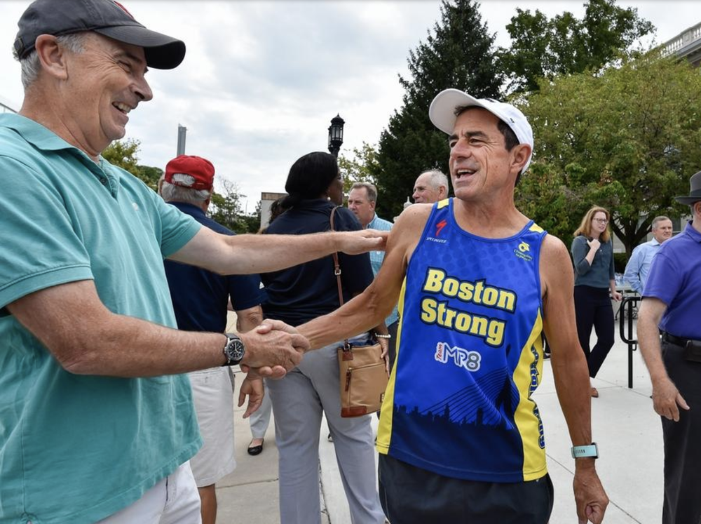 Dave Nichols shakes hands with his friend Dave McGillivray during a pre-run celebration at Medford City Hall before running from Medford City Hall to Fenway Park to commemorate his 40th Anniversary of running from Medford, Oregon to Medford, MA to raise money for the Jimmy Fund, on Thursday, Aug. 23, 2018. [Wicked Local Staff Photo / David Sokol]