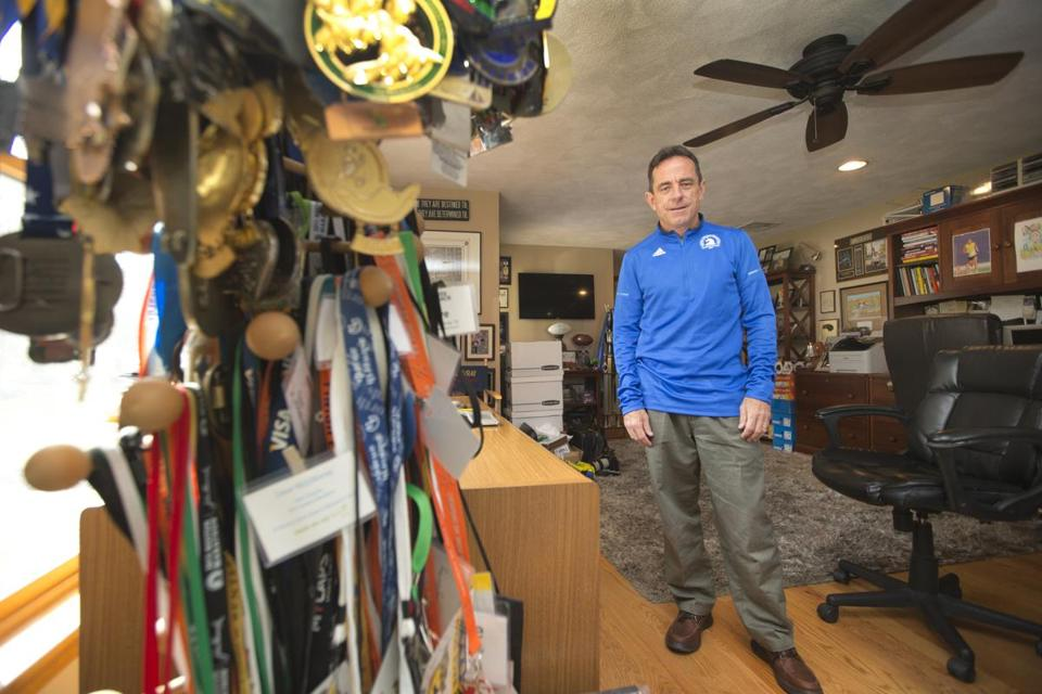 Boston Marathon race director Dave McGillivray's home office is filled with trophies and medals from some of his 145 marathons.  STAN GROSSFELD/GLOBE STAFF
