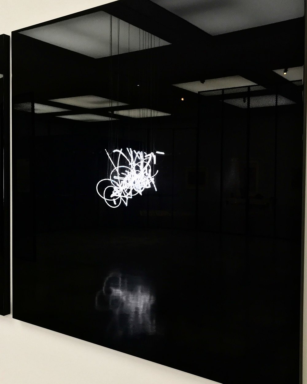 Cerith Wyn Evans 'Neon Forms (after Noh X)' reflected in Robert Irwin, 'Black Painting' | White Cube Bermondsey