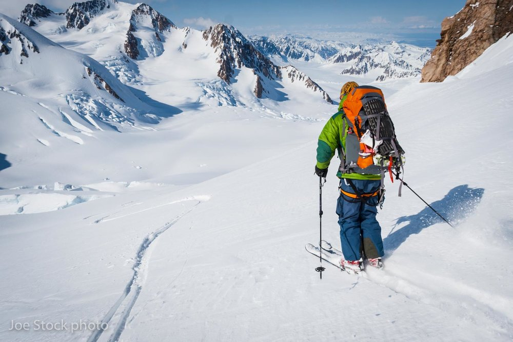Andrew skiing into the 3,000-foot Trimble Glacier icefall from near the summit of Mount Gerdine. Martin Peak in the near distance, central Alaska Range in far distance.